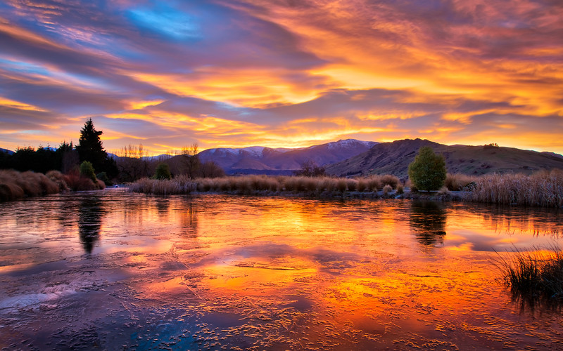 colorful-sunrise-frozen-pond-lake-hayes-estate-new-zealand.jpg