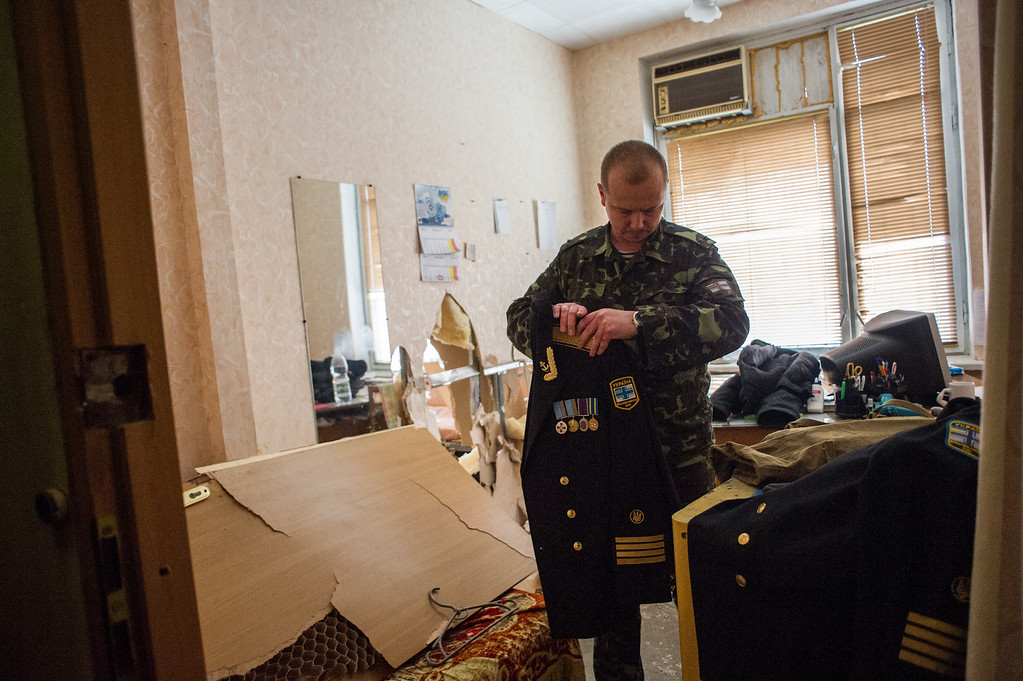 . A Ukrainian serviceman packs his things in the Ukrainian navy headquarters after it was stormed by Crimean pro-Russian self-defense forces in Sevastopol, Crimea, Wednesday, March 19, 2014. (AP Photo/Andrew Lubimov)