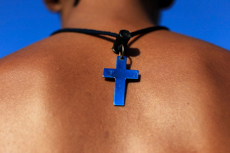 . A cross necklace is seen at the back of a lifeguard before the annual Paso del Hombre endurance challenge at La Libertad port in El Salvador February 24, 2013. About 370 male and female lifeguard volunteers swam for four to five hours continuously during the 49th edition of the event organized by the Salvadorian Red Cross in collaboration with the Navy, Coast Guard, Air Force and Civil National Police, local media reported. REUTERS/Ulises Rodriguez