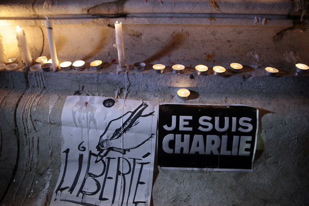 ". Picture taken of candles and placards reading in French ""Liberty\"" (L) and \""I am Charlie\"" (R) during a gathering at the Place de la Republique (Republic square) in Paris, on January 7, 2015, following an attack by unknown gunmen on the offices of the satirical weekly, Charlie Hebdo. France\'s Muslim leadership sharply condemned the shooting at the Paris satirical weekly that left at least 12 people dead as a \""barbaric\"" attack and an assault on press freedom and democracy. AFP PHOTO / JOEL  SAGET/AFP/Getty Images"