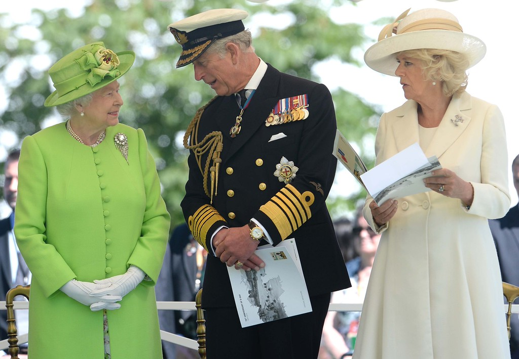 . Britain\'s Queen Elizabeth II (L), Britain\'s Prince Charles, Prince of Wales (C) and his wife Camilla, the Duchess of Cornwall Camilla (R) attend a bi-national France-UK D-Day commemoration ceremony at the British War Cemetery of Bayeux, on June 6, 2014, marking the 70th anniversary of the World War II Allied landings in Normandy. AFP PHOTO / POOL / THOMAS  BREGARDIS/AFP/Getty Images