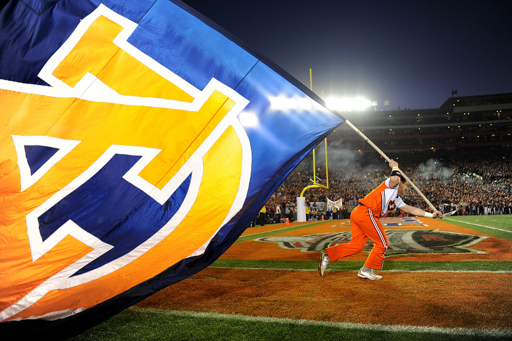 . Auburn cheerleader Charles Jacobs starts his run with the flag before the start of the BCS national championship game at the Rose Bowl, Monday, January 6, 2014. (Photo by Michael Owen Baker/L.A. Daily News)