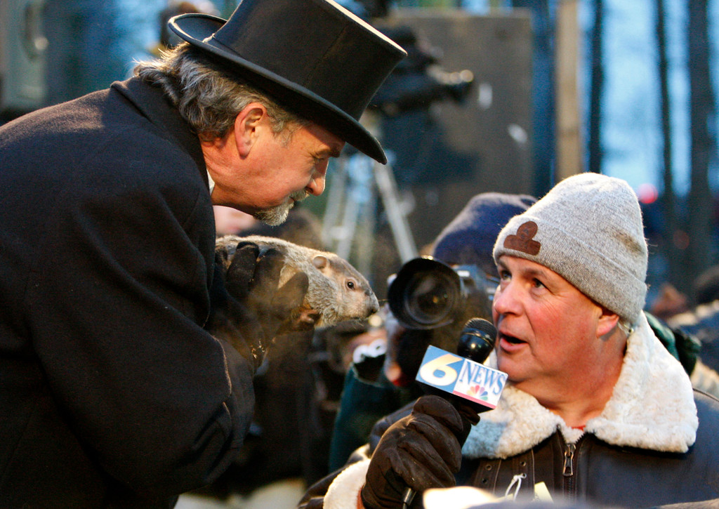 . Punxsutawney Phil, center,  is held by John Griffiths, left, as he is interviewed  after emerging from his burrow on Gobblers Knob in Punxsutawney, Pa., to see his shadow and forecast six more weeks of winter weather Tuesday, Feb. 2, 2010.  (AP Photo/Gene J. Puskar)