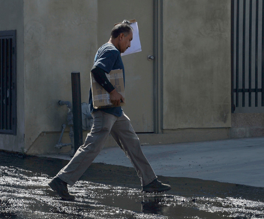. Fernando Romon  does not let the oil spill keep him from making his morning delivery in  Atwater Village on Thursday, May 15, 2014, after a 20-inch above-ground pipeline ruptured, spewing over 10,000 gallons of crude oil onto streets over a half-mile area.  (Photo by Gene Blevins/Los Angeles Daily News)