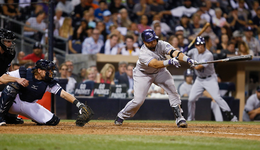 . Colorado Rockies\' Wilin Rosario strikes out to end the top of the eighth inning against the San Diego Padres with two runners in scoring position in a baseball game Wednesday, Sept. 24, 2014, in San Diego. The Padres catcher is Adam Moore. (AP Photo/Lenny Ignelzi)