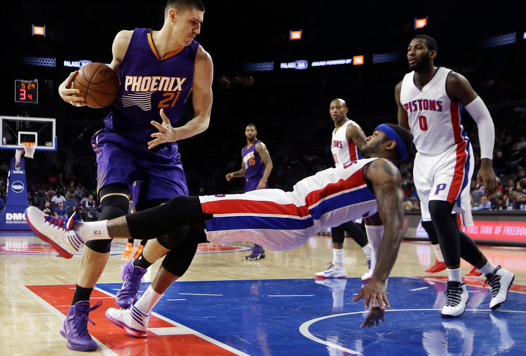 . Detroit Pistons forward Josh Smith, center, is fouled by Phoenix Suns center Alex Len (21) of Ukraine during the second half of an NBA basketball game in Auburn Hills, Mich., Wednesday, Nov. 19, 2014. (AP Photo/Carlos Osorio)