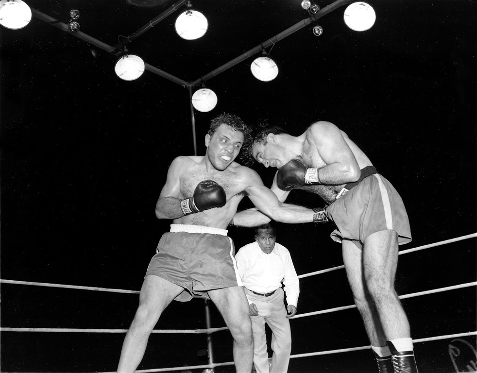 . FILE - In this June 16, 1949, file photo, Jake LaMotta, left, pounds Marcel Cerdan in third round of a world middleweight title bout in Detroit, Mich. LaMotta won the title by a knockout in the tenth round. LaMotta, whose life was depicted in the film �Raging Bull,� died Tuesday, Sept. 19, 2017, at a Miami-area hospital from complications of pneumonia. He was 95. (AP Photo/File)