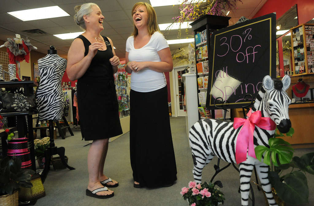 ". Glenette Sperry, left, and her daughter Tanika Bender, store owners of Floral Creations in Lindstrom, Minnesota, talk about how the colors and theme in their store is similar to the chair ""Petals & Stripes\"" out front Friday July 26, 2013. (Pioneer Press: Jean Pieri)"