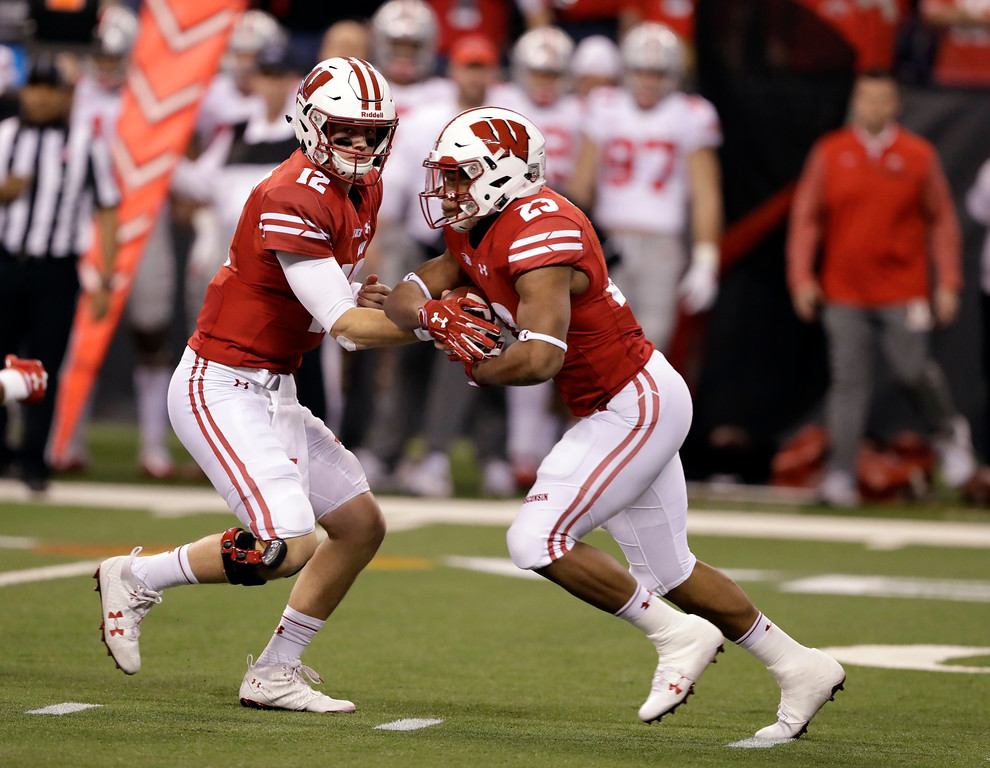 . Wisconsin quarterback Alex Hornibrook, left, hands off to running back Jonathan Taylor during the first half the Big Ten championship NCAA college football game against Ohio State, Saturday, Dec. 2, 2017, in Indianapolis. (AP Photo/Darron Cummings)
