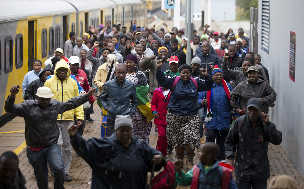 . JOHANNESBURG, SOUTH AFRICA - DECEMBER 10:  Members of the public celebrate as they arrive at Nasrec Station by train to attend the Nelson Mandela memorial service at the FNB Stadium, on December 10, 2013 in Johannesburg, South Africa. Over 60 heads of state have travelled to South Africa to attend a week of events commemorating the life of former South African President Nelson Mandela. Mr Mandela passed away on the evening of December 5, 2013 at his home in Houghton at the age of 95. Mandela became South Africa\'s first black president in 1994 after spending 27 years in jail for his activism against apartheid in a racially-divided South Africa.  (Photo by Oli Scarff/Getty Images)