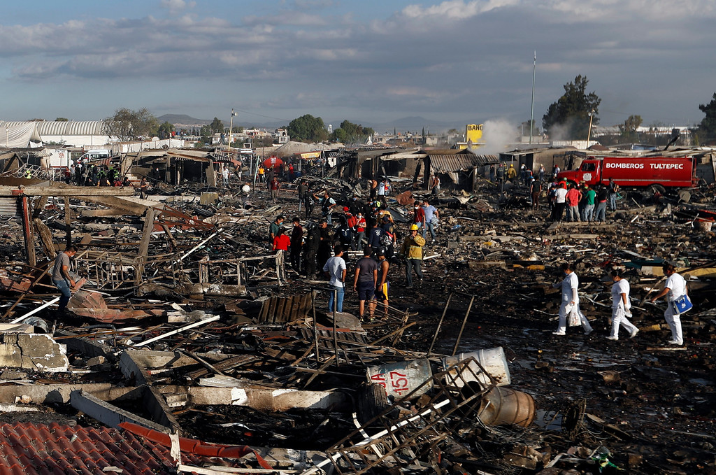 . Firefighters and rescue workers walk through the scorched ground of Mexico\'s best-known fireworks market after an explosion explosion ripped through it, inTultepec, Mexico, Tuesday, Dec. 20, 2016. National Civil Protection Coordinator Luis Felipe Puente told Milenio TV that dozens were hurt but he had no immediate report of any fatalities at the open-air San Pablito Market in Tultepec, in the State of Mexico. (AP Photo/Eduardo Verdugo)