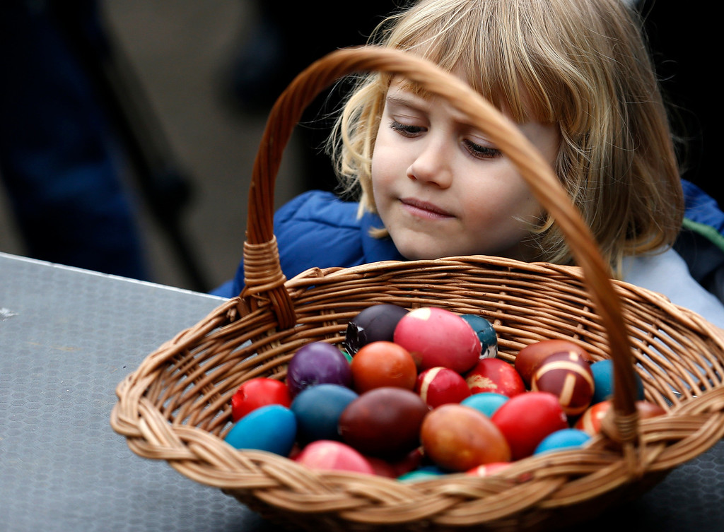 . A girl watches decorated Easter eggs as a part of a tradition of celebrating Easter in the village of Mokrin, 120 kilometers (75 miles) north of Belgrade, Serbia, Sunday, April 20, 2014. Egg cracking contest, an ancient folk tradition, takes place in this northern Serbian village. Two people bang dyed hard-boiled eggs together. The egg that cracks first is the loser; the other goes on to knock again. (AP Photo/Darko Vojinovic)