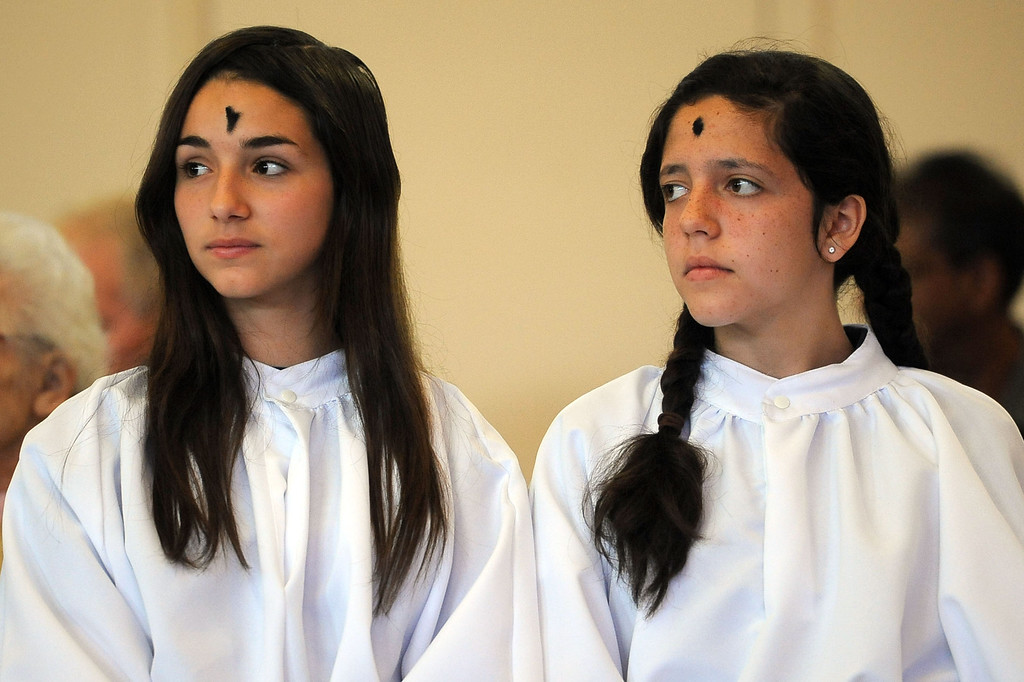 . Altar servers Natalia Vajnar and Sarah Cox (l-r) look on during the Ash Wednesday Mass at the Saint Euphrasia Catholic Church in Granada Hills, CA March 5, 2014.(Andy Holzman/Los Angeles Daily News)