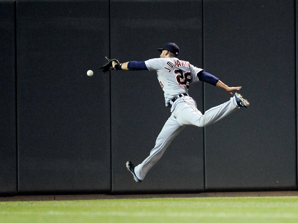 . Detroit Tigers left fielder J.D. Martinez jumps but misses a double hit by Minnesota Twins Brian Dozier during the seventh inning of a baseball game Saturday, Aug. 23, 2014, in Minneapolis. The Tigers win 8-6. (AP Photo/Craig Lassig)