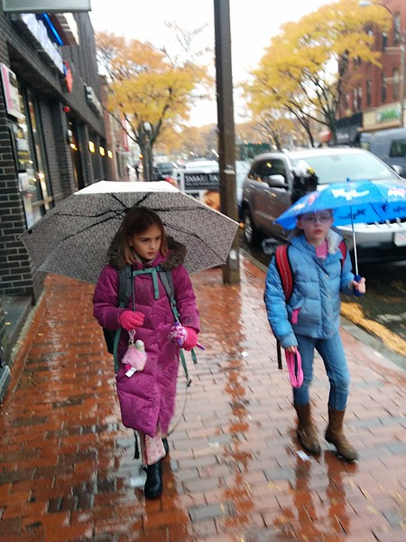 Anya and Alice in the rain on the way to school.