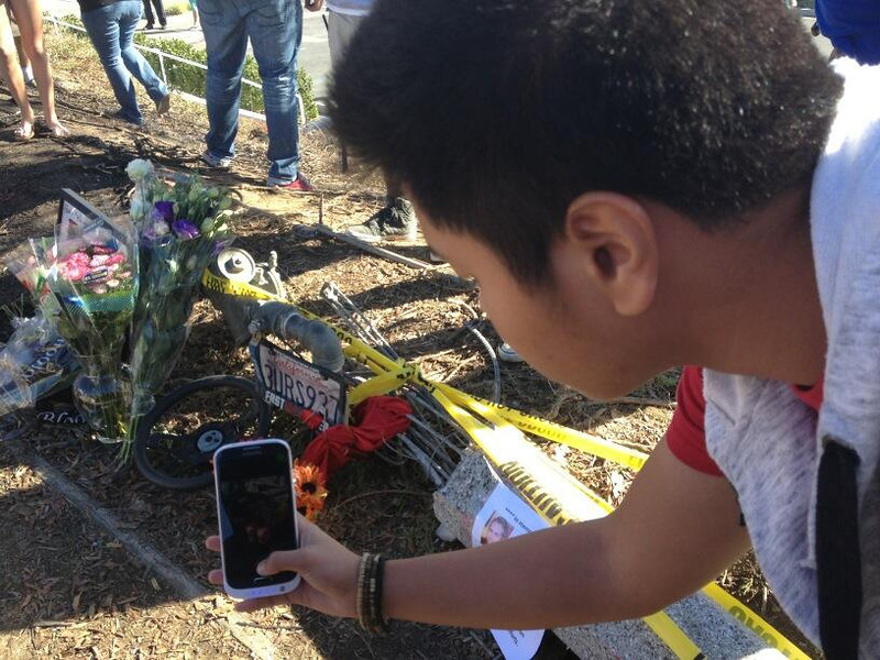 . A man takes a photo on Dec. 1, 2013, of the makeshift memorial for actor Paul Walker and his business partner, racecar driver Roger Rodas, who died in a fiery crash in Valencia on Nov. 30. (Photo by Brenda Gazzar/Los Angeles Daily News)