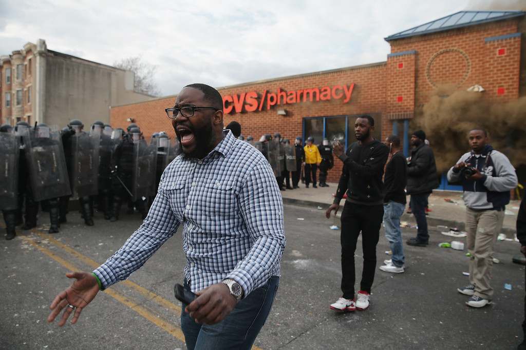 . BALTIMORE, MD - APRIL 27:  A man shouts calm as protesters face off with Baltimore Police as a CVS pharmacy burns at the corner of Pennsylvania and North avenues during violent protests following the funeral of Freddie Gray April 27, 2015 in Baltimore, Maryland. Gray, 25, who was arrested for possessing a switch blade knife April 12 outside the Gilmor Homes housing project on Baltimore\'s west side. According to his attorney, Gray died a week later in the hospital from a severe spinal cord injury he received while in police custody.  (Photo by Chip Somodevilla/Getty Images)