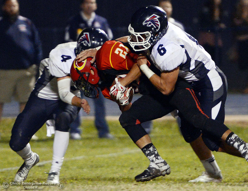 . Chico High\'s #21 Cameron Alfaro (center) is tackled against Central Valley High\'s #4 Timmy Naylor (left) and #6 Connor Silveria (right) in the first quarter of their football game at Asgard Yard Friday, September 27, 2013, in Chico, Calif.  (Jason Halley/Chico Enterprise-Record)