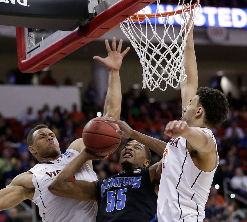 . Memphis guard Geron Johnson (55) shoots against Virginia\'s Justin Anderson, left, and Anthony Gill (13) during the first half of an NCAA college basketball third-round tournament game, Sunday, March 23, 2014, in Raleigh. (AP Photo/Chuck Burton)