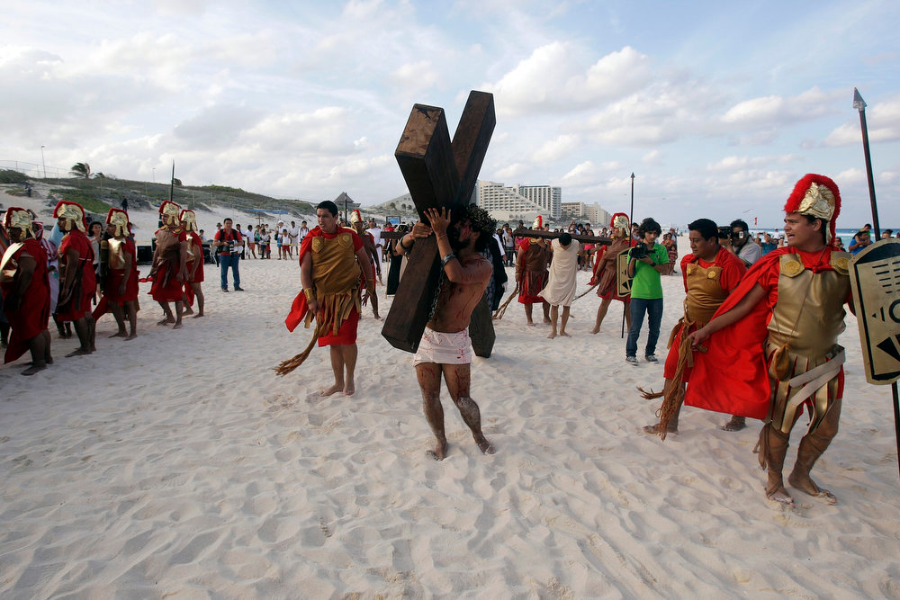 . An actor playing the role of Jesus Christ carries a cross during a re-enactment of the crucifixion of Jesus Christ at Playa Delfines (Dolphin Beach) on Good Friday in Cancun March 29, 2013. Holy Week is celebrated in many Christian traditions during the week before Easter. REUTERS/Victor Ruiz Garcia