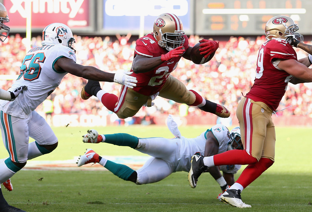 . SAN FRANCISCO, CA - DECEMBER 09: Anthony Dixon #24 of the San Francisco 49ers leaps over Chris Clemons #30 of the Miami Dolphins at Candlestick Park on December 9, 2012 in San Francisco, California.  (Photo by Ezra Shaw/Getty Images)