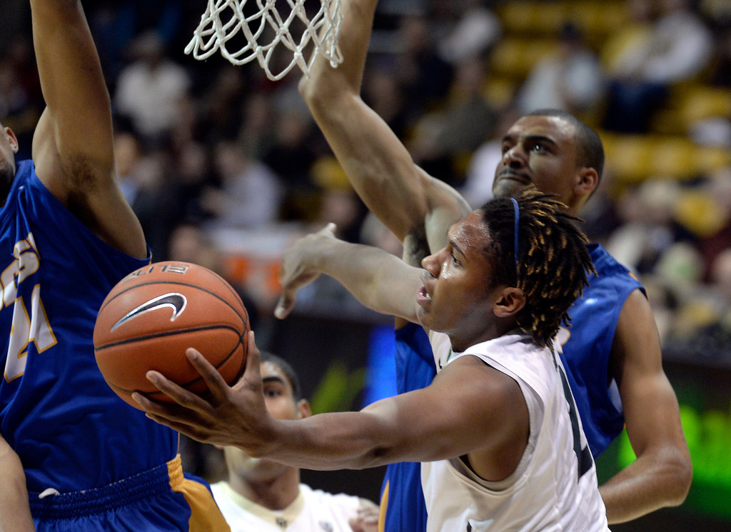 . University of Colorado\'s Xavier Johnson goes for a layup in front of Taran Brown, at right, during a game against  the University of California Santa Barbara, on Nov. 20, at the Coors Event Center in Boulder.  (Jeremy Papasso/Boulder Daily Camera)