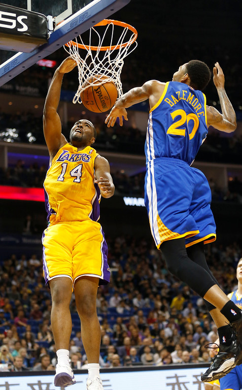 . Marcus Landry of Los Angeles Lakers, left, scores against Kent Bazemore of Golden State Warriors, right, during a 2013-2014 NBA preseason game between Lakers and Warriors at Mercedes-Benz Arena in  Shanghai, China, Friday, Oct. 18, 2013. (AP Photo/Eugene Hoshiko)