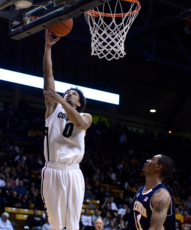 . University of Colorado\'s Askia Booker goes for a layup over Gabe Rogers during a game against Northern Arizona on Friday, Dec. 21, at the Coors Event Center on the CU campus in Boulder.    (Jeremy Papasso/Daily Camera)