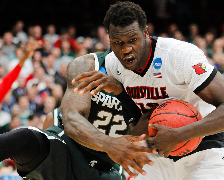 . Louisville\'s Mangok Mathiang, right, of Australia, protects the ball from Michigan State\'s Branden Dawson (22) during the second half of a regional final in the NCAA men\'s college basketball tournament Sunday, March 29, 2015, in Syracuse, N.Y. (AP Photo/Nick Lisi)