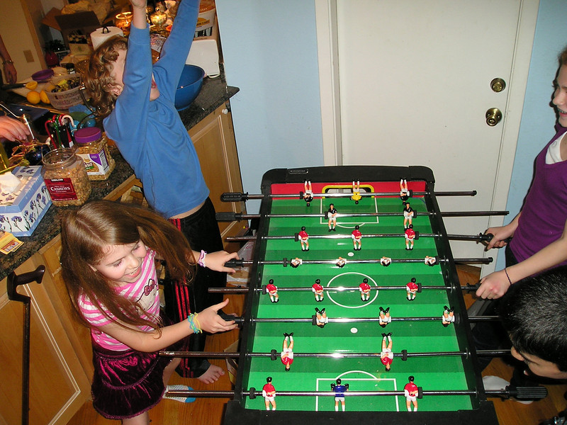 Alex and friends play foosball, and Alex has apparently scored a major victory.