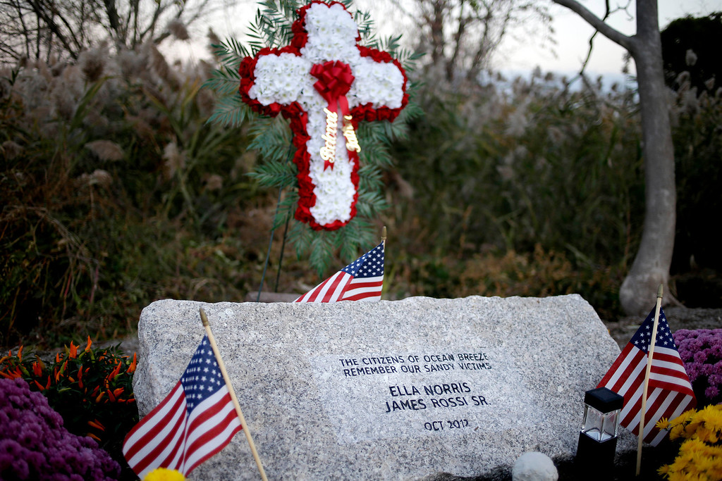 . A memorial stone that honors two victims of Superstorm Sandy from the Ocean Breeze neighborhood is surrounded by flowers and flags in Staten Island, New York, Tuesday, Oct. 29, 2013.  (AP Photo/Seth Wenig)