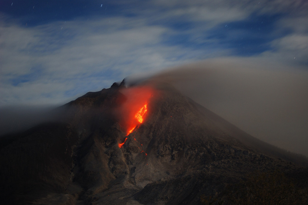 . Molten lava rolls down from the crater of Mount Sinabung volcano during an eruption on October 8, 2014, as seen from Karo district located on Indonesia\'s Sumatra island, following an earlier eruption on October 5, 2014.  AFP PHOTO / SUTANTA ADITYA/AFP/Getty Images