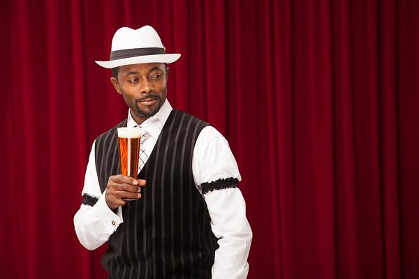 african american bartender in retro suit with beer