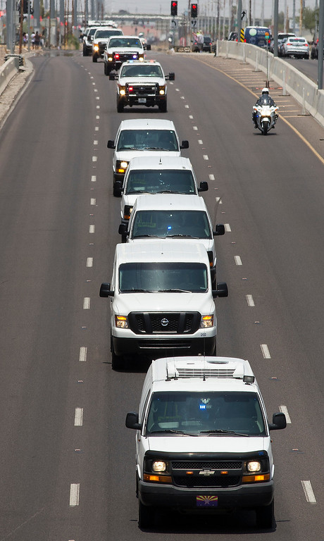 . A procession carrying the bodies of the firefighters who died Sunday fighting the Yarnell Hill Fire heads down Grand Avenue toward the Maricopa County Medical Examiner\'s office on Monday, July 1, 2013.  (AP Photo/The Arizona Republic, Mark Henle)