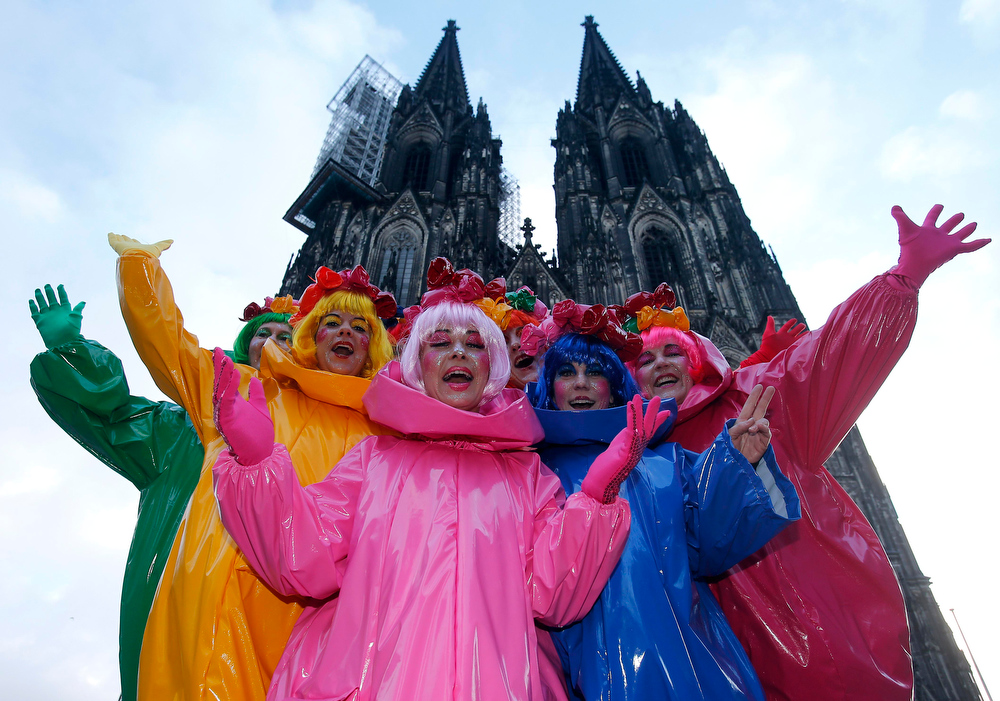 """Description of . Carnival revellers stand in front of the Cologne cathedral while they celebrate the start  of the street-carnival with its tradition of fools entering the town halls and women cutting off men\'s ties with scissors on carnival\'s so called \""""Old Women\'s Day\"""" in Cologne, Germany, Thursday, Feb. 7, 2013. The \""""Old Women\'s  Day\""""  is traditionally the beginning of  street carnival, the foolish street spectacles in the carnival centers of Duesseldorf, Mainz and Cologne. (AP Photo/Frank Augstein)"""