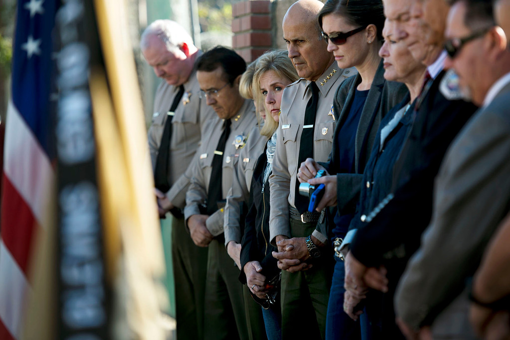 . Teresa Lee, wife of Deputy Dave March, center, during Deputy Dave March Memorial Re-Dedication Ceremony in Irwindale on Wednesday, Dec. 11, 2013. The memorial was destroyed on Thanksgiving when a driver fell asleep at the wheel and crashed into it. (Staff photo by Watchara Phomicinda/ San Gabriel Valley Tribune)