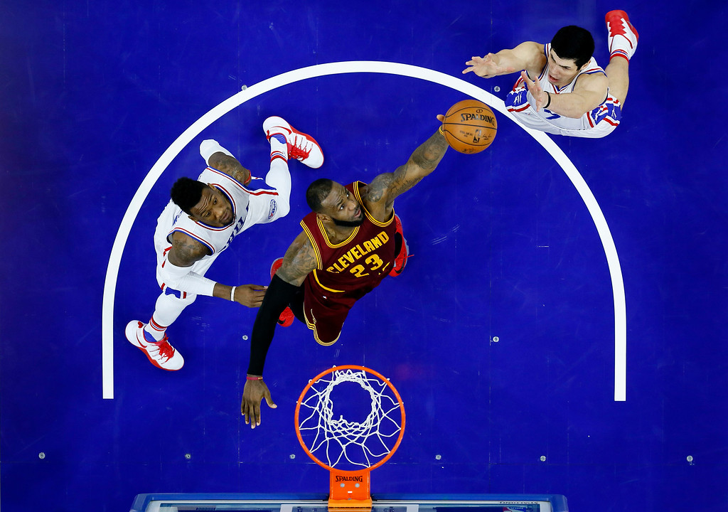 . Cleveland Cavaliers\' LeBron James, center, leaps for a rebound against Philadelphia 76ers\' Ersan Ilyasova, right, and Robert Covington during the second half of an NBA basketball game, Sunday, Nov. 27, 2016, in Philadelphia. (AP Photo/Matt Slocum)