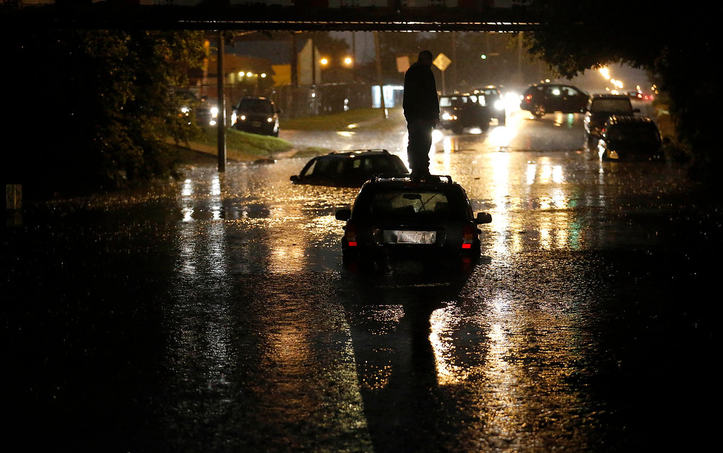 . A man stands on top of his car as it is flooded on S. May Ave near SW 25th in Oklahoma City, Friday, May 31, 2013, following flooding after a severe thunderstorm moved through Oklahoma CIty. (AP Photo/The Oklahoman, Sarah Phipps)