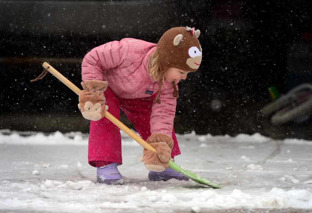 . ENGLEWOOD, CO. - MARCH 23:   Malia Mariea helps her father, Josh, shovel the driveway outside their home in Englewood, CO March 23, 2013. The Saturday forecast calls for snow accumulation of 9 to 12 inches with highs in the lower to mid 20s. (Photo By Craig F. Walker/The Denver Post)