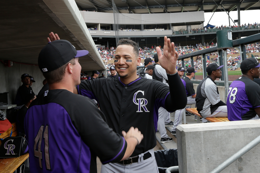 . Colorado Rockies\' Ryan Casteel, left, gets a hug from Carlos Gonzalez, center right, after Casteel hit a home run against the Arizona Diamondbacks during the third inning in a spring training baseball game Friday, Feb. 28, 2014, in Scottsdale, Ariz. (AP Photo/Gregory Bull)