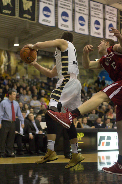 . #13 Mitch Baenzinger grabs a rebound from a Rochester College player. Photo by Dylan Dulberg
