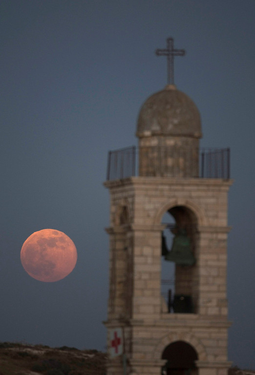 ". The moon is seen rising behind the Mar Elias Greek Orthodox Monastery in Jerusalem on June 23, 2013. The largest full moon of the year, called a ""super moon,\"" will light up the night sky this weekend.  REUTERS/Darren Whiteside"