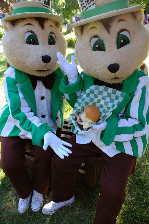 . State Fair mascots Fairchild and Fairborne posing with a sandwich during the 2010 Minnesota State Fair. Photo courtesy of the Minnesota State Fair.