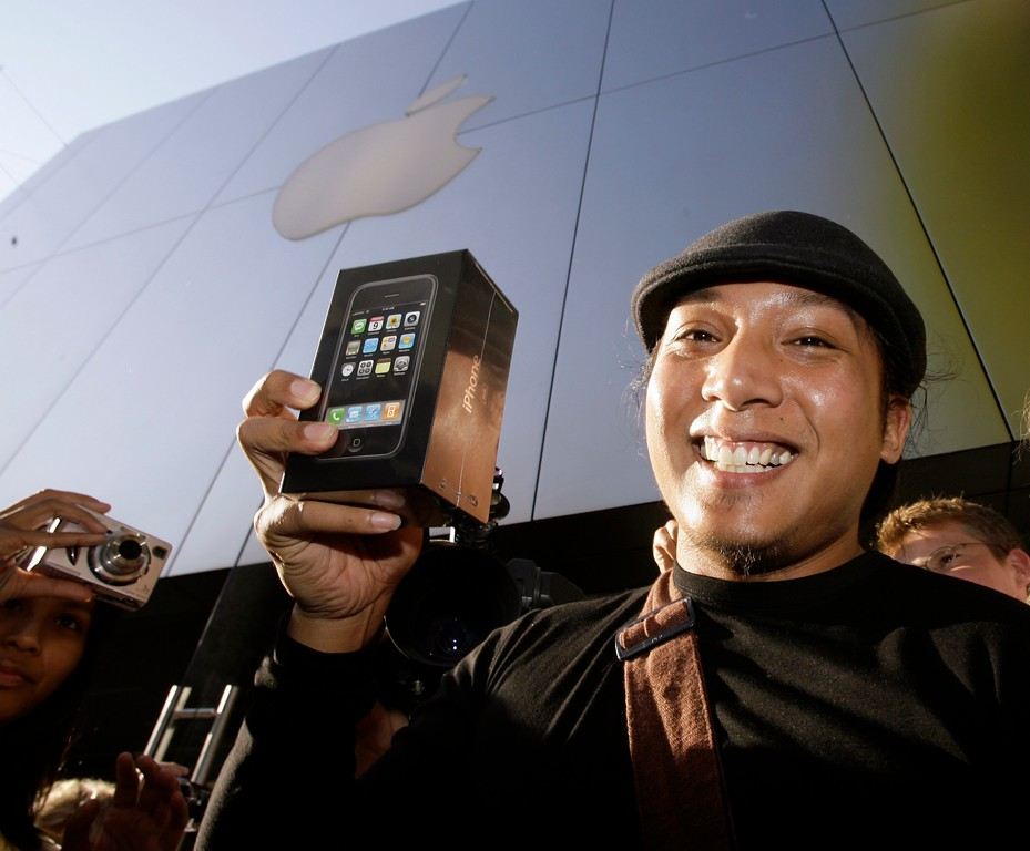 . First in line John Mariano, 27, is surrounded by onlookers and media as he leaves the Apple Store with his newly purchased iPhone Friday, June 29, 2007, at The Grove shopping center in Los Angeles. (AP Photo/Damian Dovarganes)