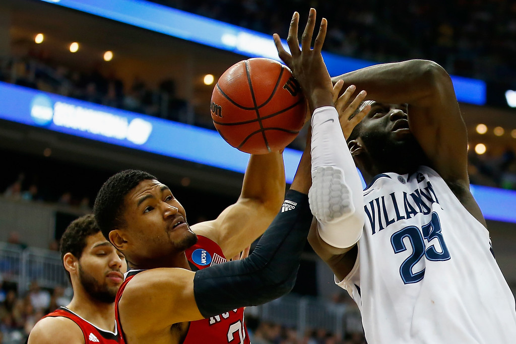 . Kyle Washington #32 of the North Carolina State Wolfpack and Daniel Ochefu #23 of the Villanova Wildcats go after the ball in the first half during the third round of the 2015 NCAA Men\'s Basketball Tournament at Consol Energy Center on March 21, 2015 in Pittsburgh, Pennsylvania.  (Photo by Jared Wickerham/Getty Images)