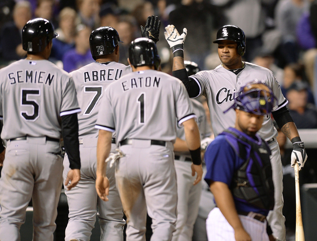 . Chicago slugger Jose Abreu was met at the plate by teammates following his 3-run home run off Colorado reliever Chad Bettis in the seventh inning.   (Photo by Karl Gehring/The Denver Post)
