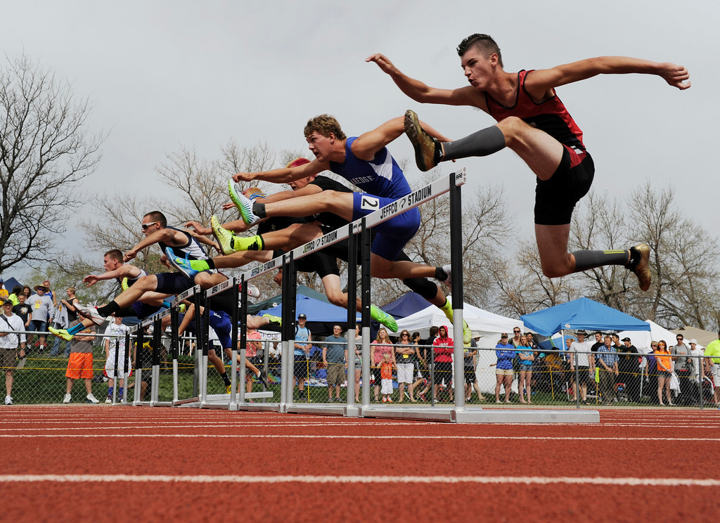 . Trevor Lyons, right,  of Strasburg High School, heads over a hurdle for the start of the boys 3A 110 meter hurdles at the at the Colorado State Track and Field Championships at Jeffco Stadium, Saturday morning, May 18, 2013.  (AP Photo/The Denver Post, Andy Cross)