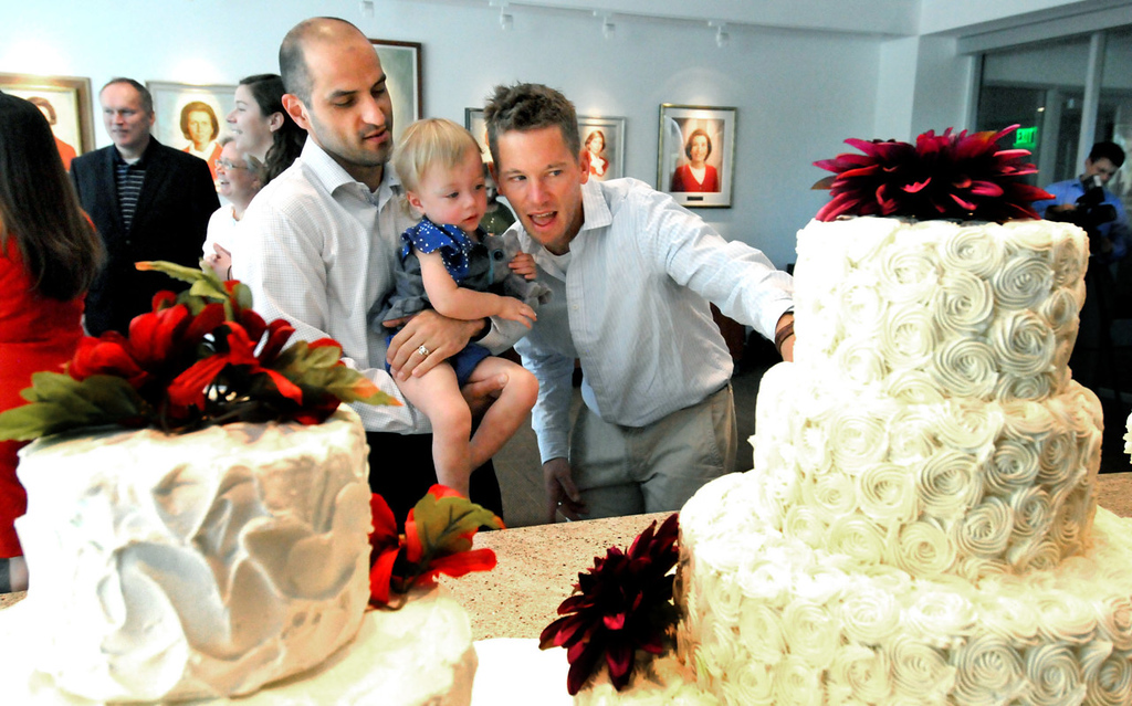 . Paul Nolle, left, daughter Anna Bordson-Nolle, 18 months, and Nolle\'s partner Reid Bordson look over cakes before cake tasting at the Betty Crocker Kitchens at General Mills headquarters in Golden Valley begins Monday, July 29, 2013. The couple were among three couples sampling the cakes. (Pioneer Press: John Doman)
