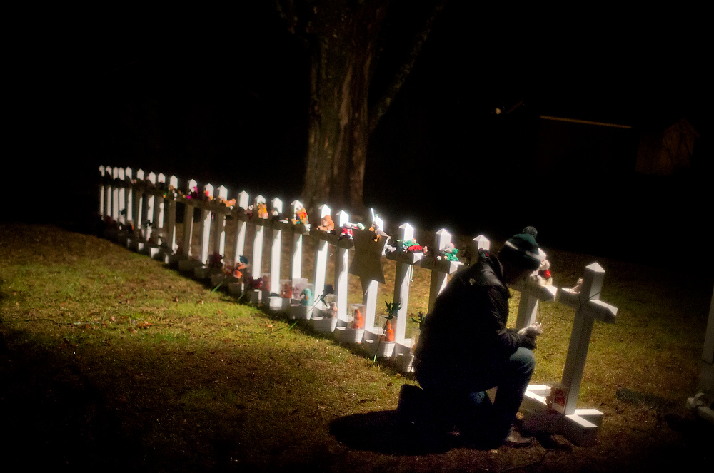 Description of . Frank Kulick, adjusts a display of wooden crosses, and a Jewish Star of David, representing the victims of the Sandy Hook Elementary School shooting, on his front lawn, Monday, Dec. 17, 2012, in Newtown, Conn. (AP Photo/David Goldman)