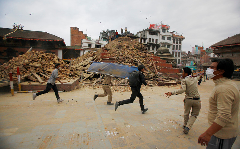 . Volunteers run with a stretcher to carry a dead body recovered from the debris of a building that collapsed after an earthquake  in Kathmandu, Nepal, Saturday, April 25, 2015. A strong magnitude-7.9 earthquake shook Nepal\'s capital and the densely populated Kathmandu Valley before noon Saturday, causing extensive damage with toppled walls and collapsed buildings, officials said. (AP Photo/ Niranjan Shrestha)